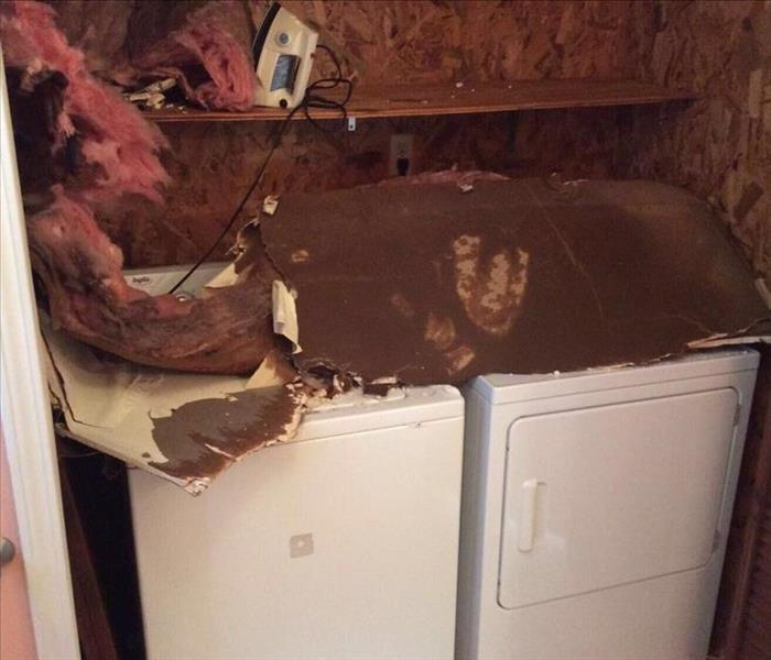 white washer and dryer in closet with drywall, ceiling debris and insulation piled on top