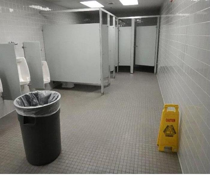 mens room floor in retail store with small gray tiles, stalls and urinals