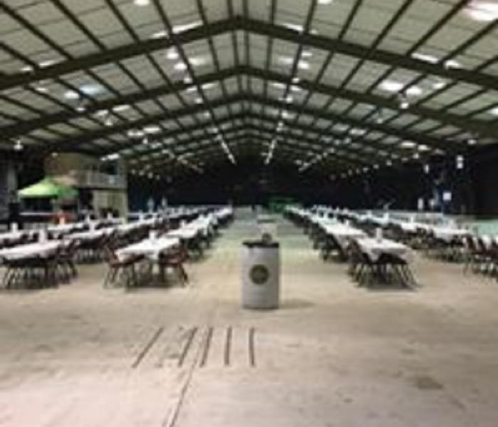long building with metal rafters, concrete floorin, rows of tables and chairs set up