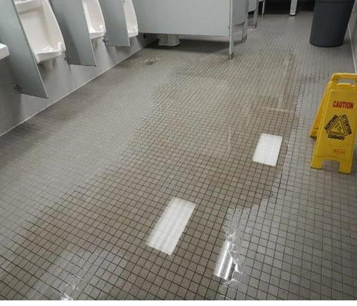 mens room floor in retail store with small square gray tiles  with standing water, stalls, urinals