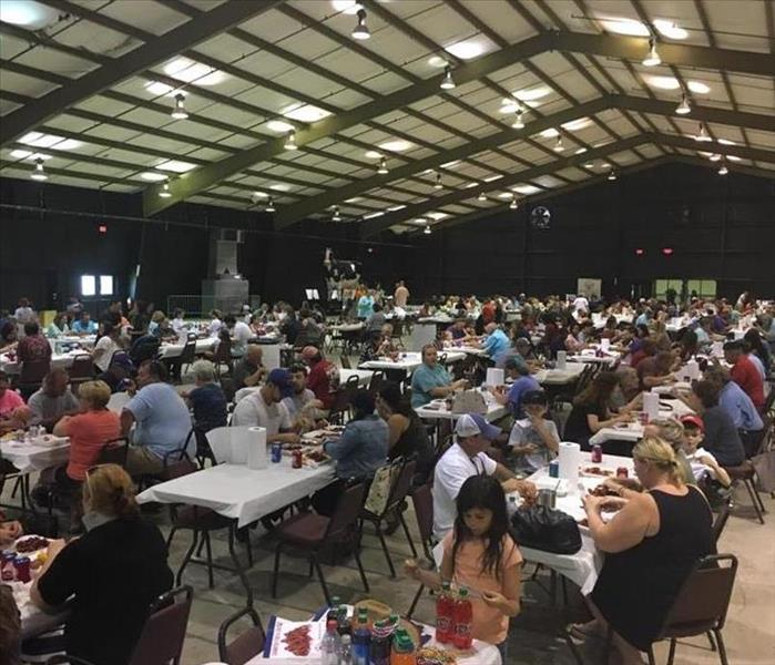 long building with metal rafters, concrete flooring, tables full of people eating crawfish