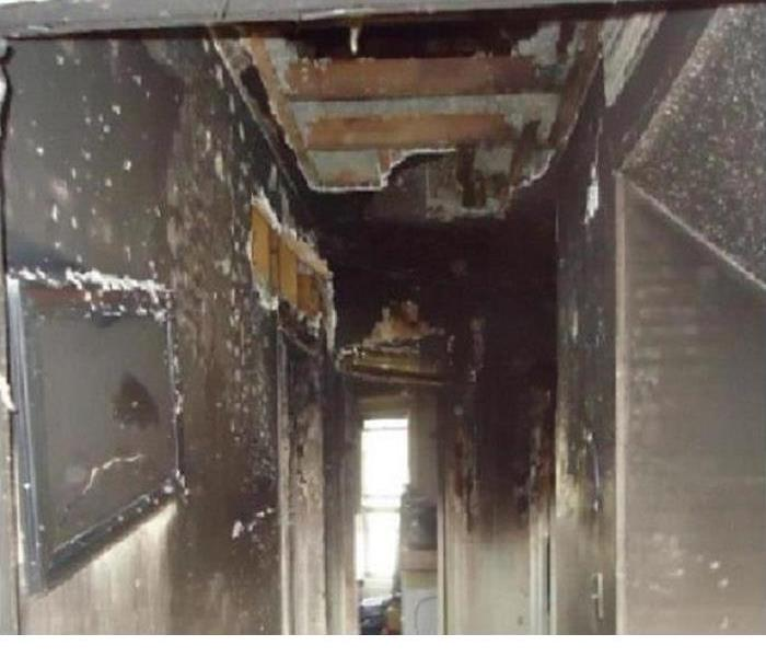 soot and fire damage on walls and ceilings of residential hall