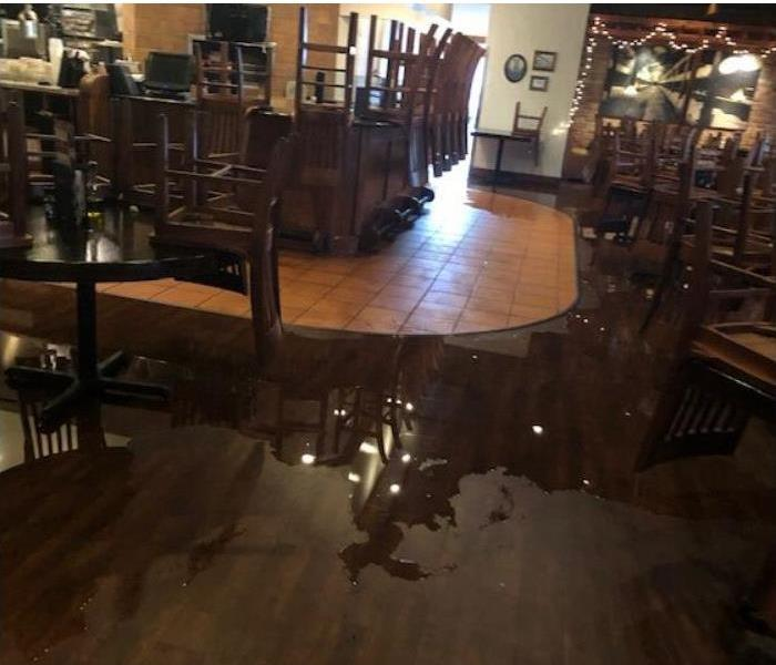 dark wood and tile floor, restaurant tables with chairs on top, standing water on floor