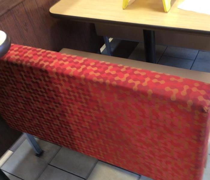 red and orange cushion covering back of bench at restaurant table cleaned with no dark stains