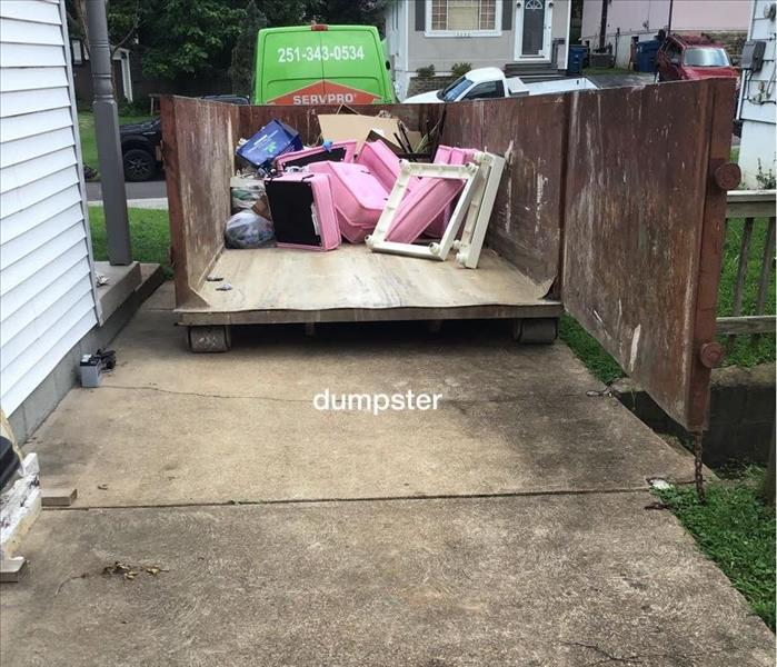 metal trash dumpster open filled with unsalvageable home furnishings