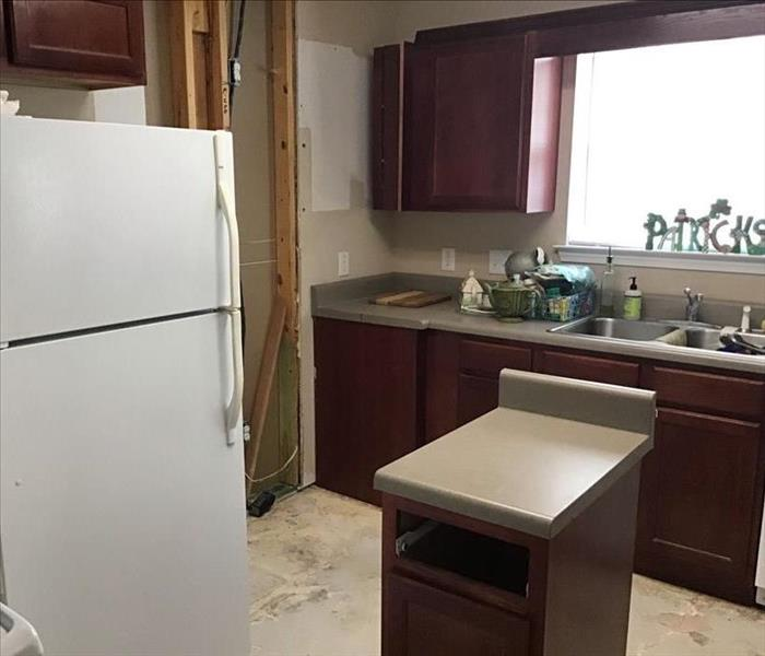 white refrigerator in kitchen with cabinetry and drywall removed