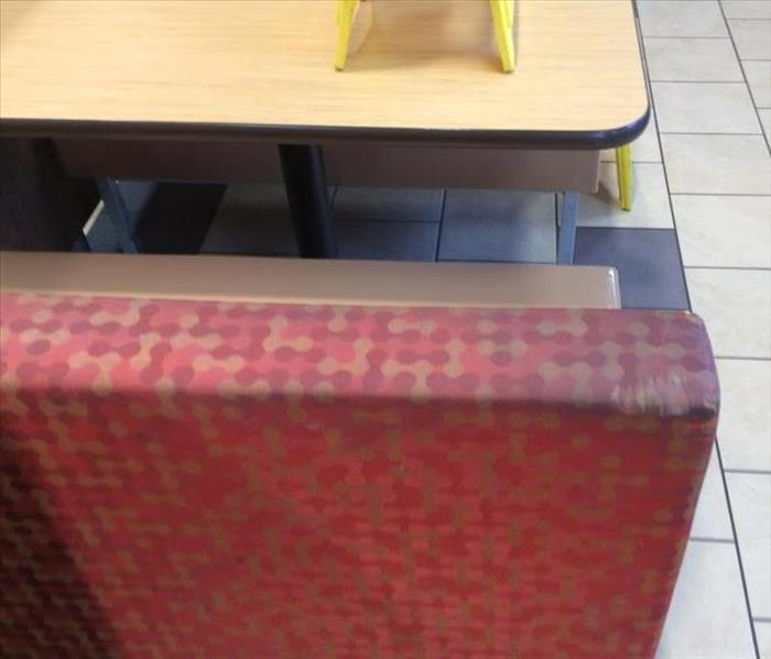 red and orange cushion covering back of bench at restaurant table with visible dark staining