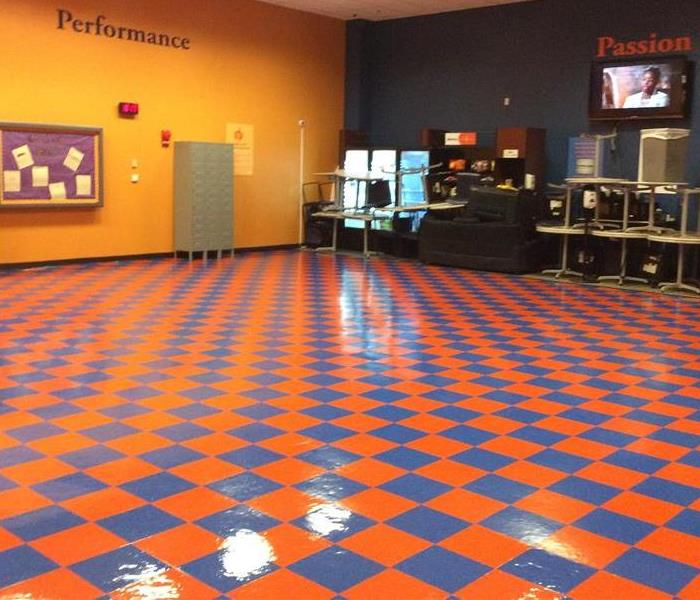 large room with shiny checkered orange and blue tile