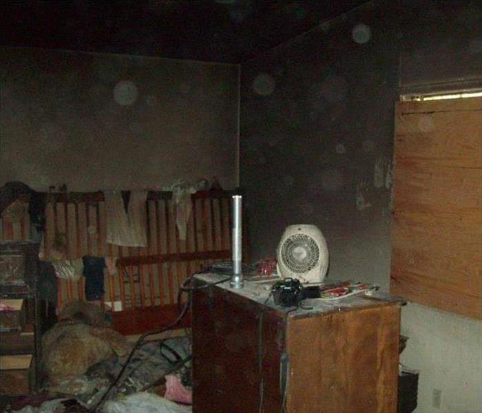 bedroom with walls covered in soot