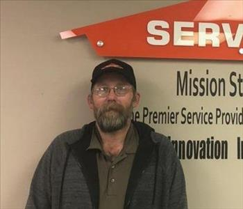 Male employee with beard and glasses smiling for the camera