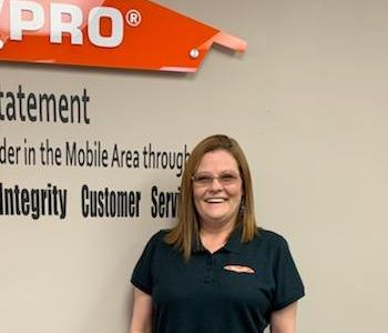 women with red hair and glasses smiling in front of servpro logo