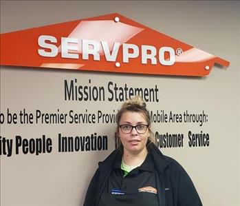 Picture of female smiling, wearing glasses in front of SERVPRO sign