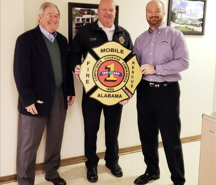3 males smiling for the camera holding fire department shield