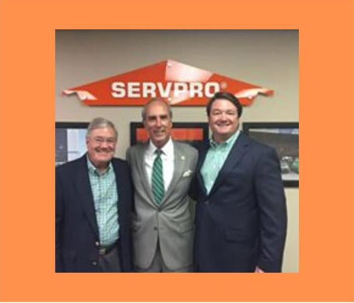 3 men smiling for camera with SERVPRO logo in background