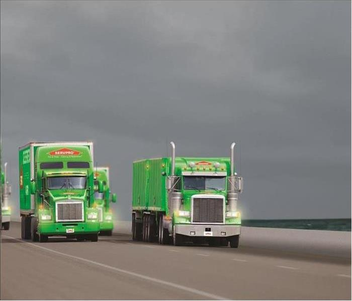 green servpro trucks on a highway