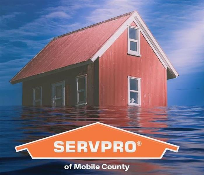 red house with water surrounding it and orange SERVPRO logo
