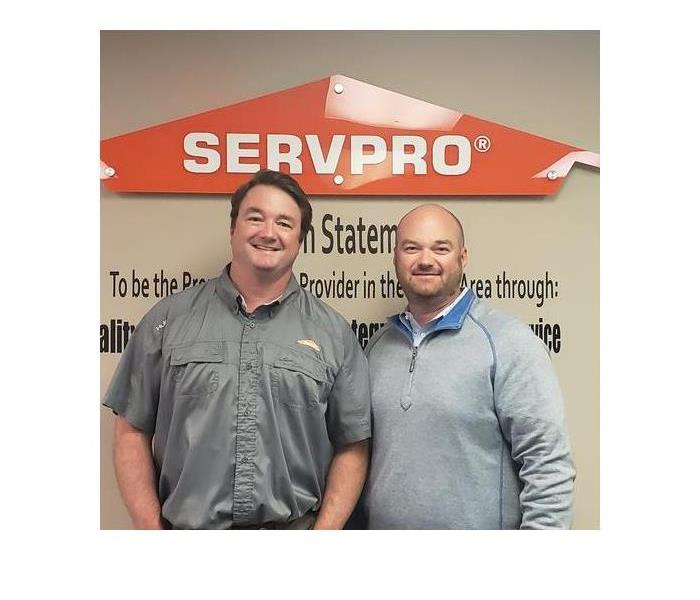 two men smiling for the camera in front of SERVPRO logo on wall