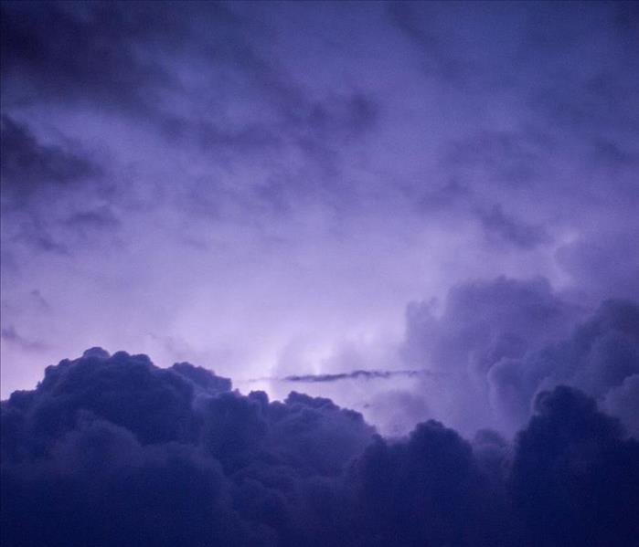 cloud formation with purple/blue sky lit up by lightning